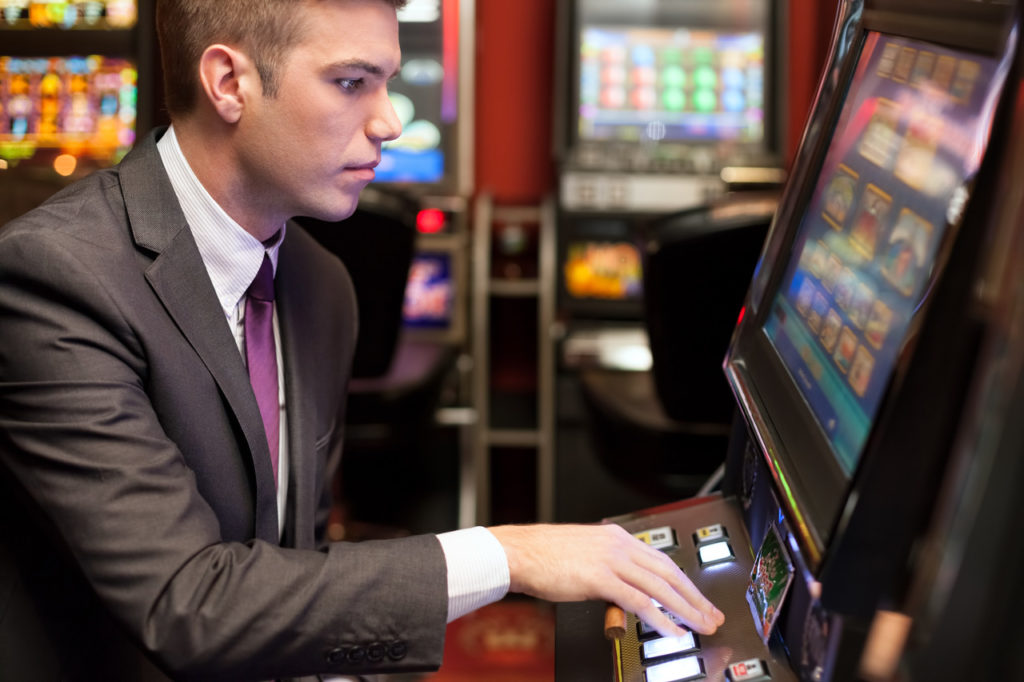Young handsome men gambling in the casino on slot machines